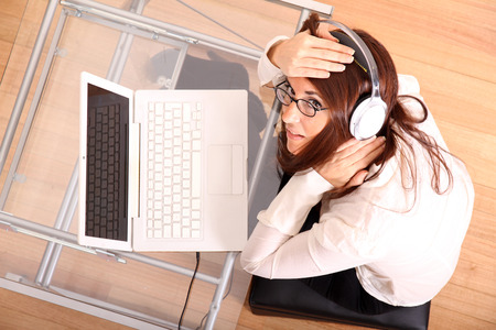 Business woman working on a Laptop while listening music with Headphones. photo