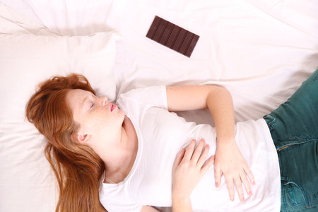 lazyness: A young adult Woman sleeping on bed with a chocolate beside her.  Stock Photo