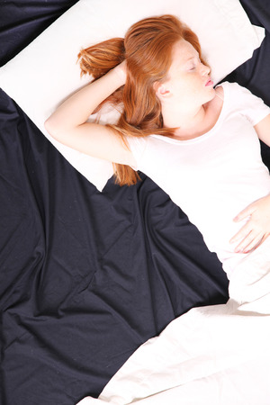 A young adult Woman sleeping on bed.  photo