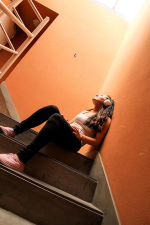 melancholijny: A young woman listening to melancholic Music sitting in the stairway. Zdjęcie Seryjne