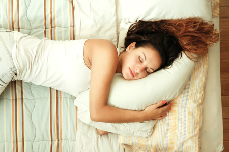 person woman: A young woman sleeping on the bed. Stock Photo