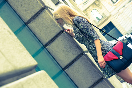 Retro style image of a young adult woman standing in front of a Store in downtown Barcelona, Spain. photo