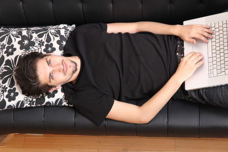 trackpad: A young hispanic man with a laptop on the Sofa. Stock Photo
