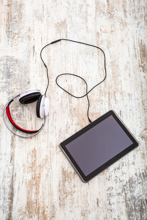 develope: A Tablet PC with headphones on the Table. Stock Photo