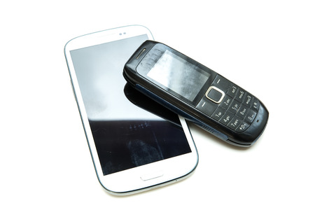 A modern smartphone and a old classic cell phone side by side. photo