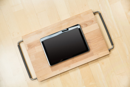 A Tablet PC on a cutting board. photo