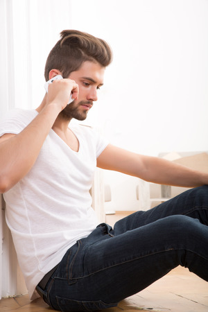 A young adult man sitting at home and talking on the phone. photo