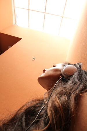 melancholijny: Młoda kobieta słuchanie muzyki melancholijnej siedzi w klatce schodowej.