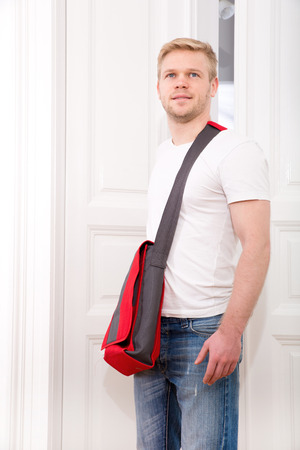 A young blonde man coming home passing through the door. photo