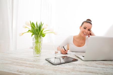 working from home: A young woman working from home with a laptop computer.