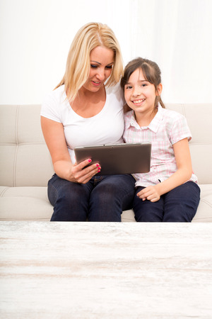 A mother using with her daughter a Tablet PC. photo