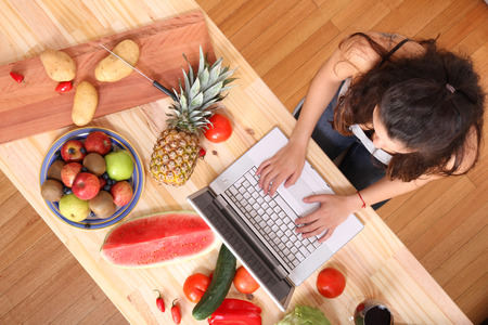 A young woman using a Laptop while cooking. Stock Photo