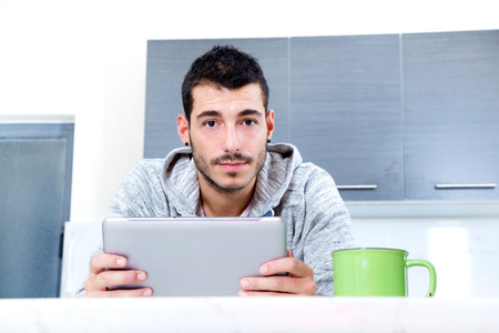 Portrait of a young man in the kitchen with a tablet.  photo