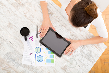 A young adult woman developing a business plan with her tablet PC at home.