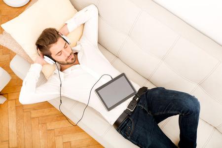 descansando: Un hombre joven y guapo en el sof� escuchando m�sica. Foto de archivo