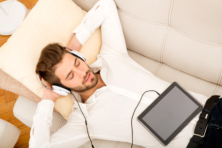 young style: A young handsome man on the couch listening to music.