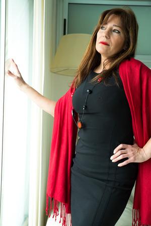 melancholijny: Melancholijny piękna kobieta dojrzała patrząc przez okno. Zdjęcie Seryjne