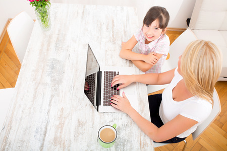 A mother with her daughter looking at a Laptop at home.  photo