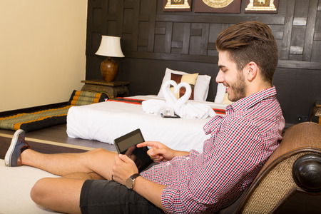 A young man using a tablet pc in a asian hotel room.  photo