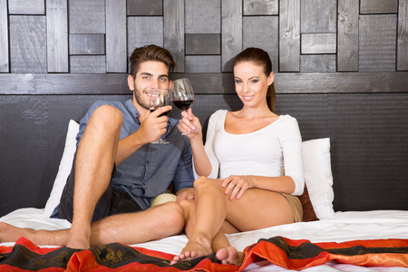 A happy young couple on their vacations with a glass of wine lying on the bed in an asian style hotel room. photo