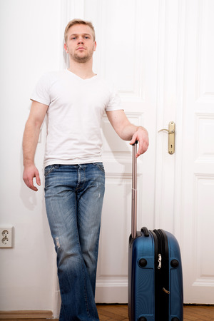 A young man going to travel with a suitcase. photo