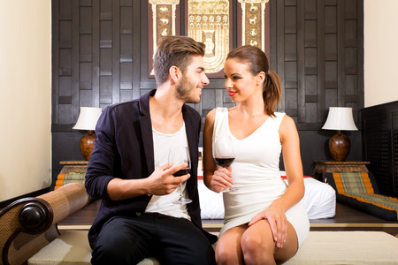 courting: A young and happy couple enjoying a glass of wine in a asian style hotel room on their vacations.