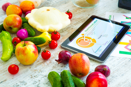 grow food: Organic food and a Tablet PC showing information about healthy nutrition and phytochemical composition.