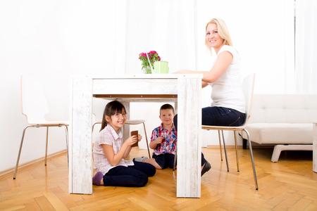 Дети едят шоколад под столом у себя дома, а мать работает. Фото со стока - 31848112