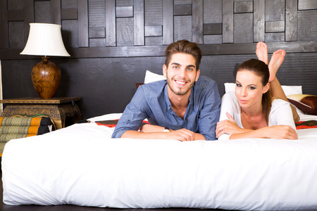 hotel room: A happy young couple on their vacations lying on the bed in an asian style hotel room. Stock Photo