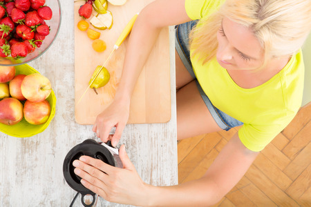 A blond mature woman blending a smoothie in the kitchen seen from above. photo