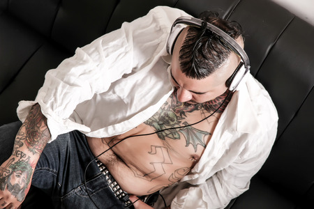 Portrait of a tattooed hispanic man sitting on the sofa and listening to music. photo