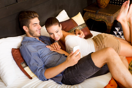 Young couple using a smartphone in a asian hotel room while lying on the bed. Stock Photo