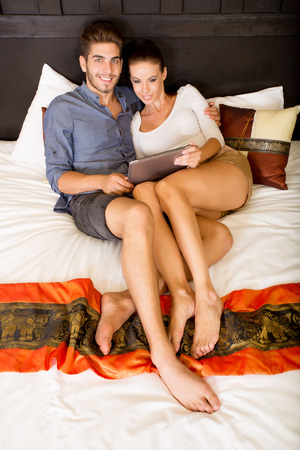 Young couple using a Tablet PC in a asian hotel room while lying on the bed. photo