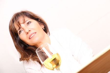 A beautiful mature woman with a glass of white wine. photo
