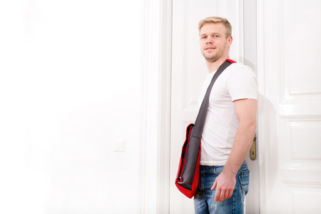 coming home: A young blonde man coming home passing through the door.