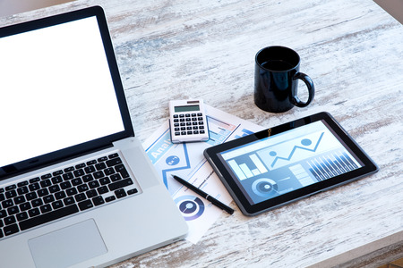 Business Analytics on a wooden Desk with a Tablet PC and a Laptop. Stock Photo