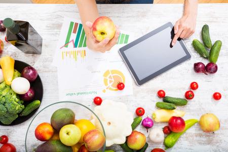 Primer plano de una mujer adulta joven informar a sí misma con un tablet PC sobre los valores nutricionales de las frutas y verduras.