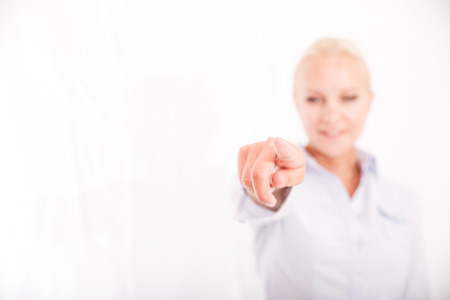 A young blonde woman pointing finger at camera. photo