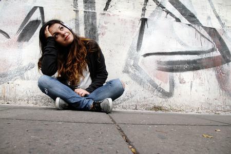 melancholic: A young woman listening to melancholic Music and sitting on the pavement.