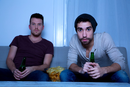 passionately: Two Friends watching passionately TV with Beer and Potato Chips.