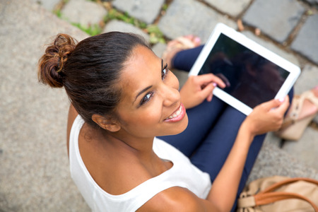 green screen: Hispanic girl using tablet in the city.