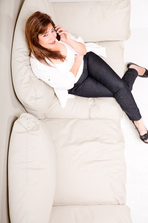 women s feet: A beautiful mature woman talking on her cell phone on the sofa