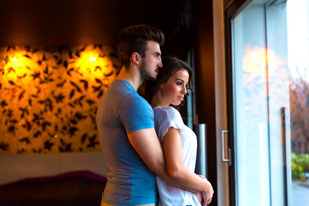 men s feet: A young couple standing at the window at home while hugging in love. Stock Photo