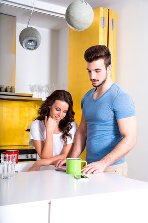 A young couple using a Tablet PC in the kitchen while having a cup of coffee. photo