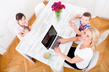 A mother working at home with a laptop and parenting her two children.