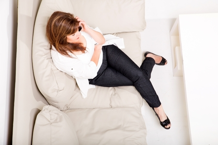 A beautiful mature woman talking on her cell phone on the sofa photo