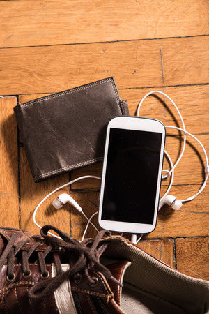 plugged in': A pair of shoes, a wallet and a smartphone with plugged in earphones on the floor.