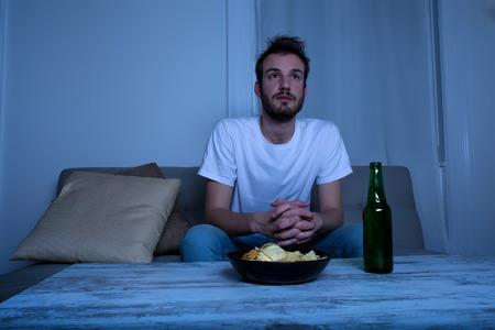 ver television: Un joven viendo la televisión en la noche con papas fritas y cerveza en casa, en la sala de estar. Foto de archivo