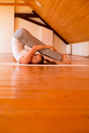 practicing: Woman practicing Yoga in a Studio Stock Photo