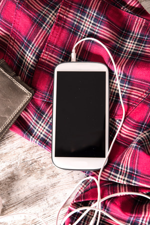 plugged in': Red pants, a wallet and a smartphone with plugged in earphones on the table.